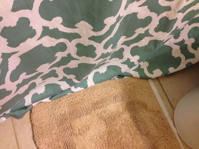 shower curtain puddled on bathroom floor