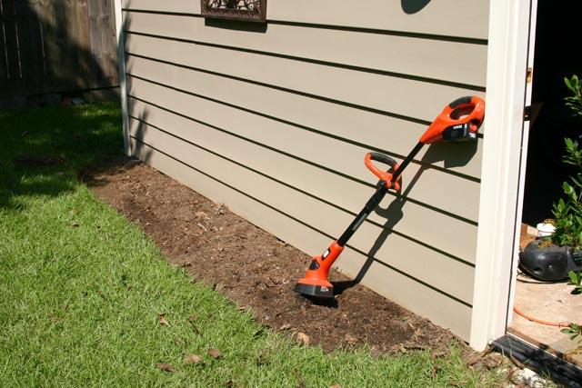 Black and Decker orange cordless tiller green grass garage vinyl siding and empty flower bed