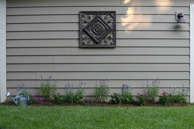 blue and purple salvia in flower bed against tan vinyl siding with brown medallion with pink and purl pentas