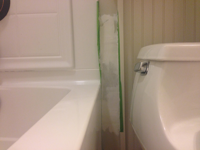 drywall in process of repair with green painter's tape near toilet and bathtub