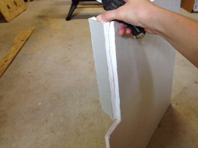 Drywall sheet cut and bent backwards, hand holding utility knife for cutting