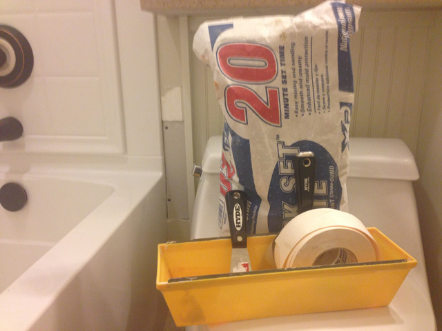 20 minute quick drywall mud with yellow drywall tray, putty knife and 6 inch mud knife and drywall paper tape sitting on toilet
