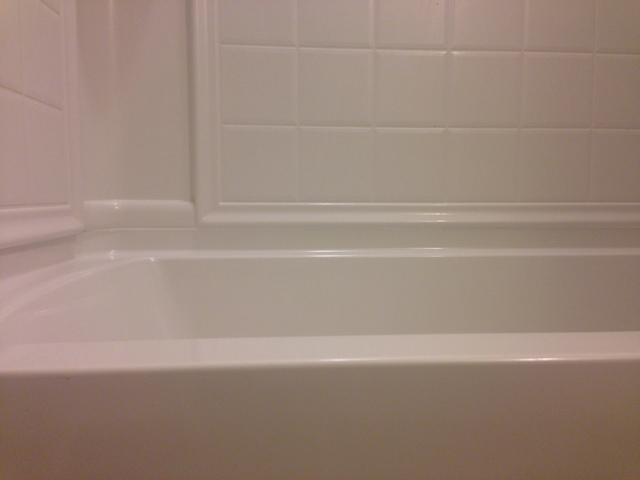bathtub corner with tile surround and fresh caulk in joints