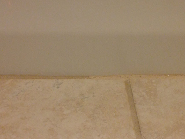 Tan bathroom tiles with new grout overlapping old grout