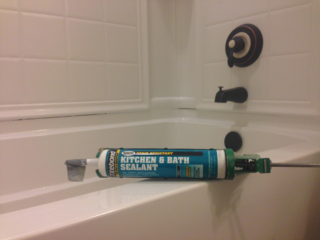 Titebond kitchen and bath sealant laying on bathtub that needs new caulk