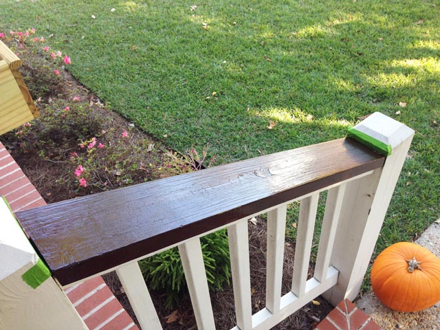 dark wood stained handrails with green painter's tape and one coat of varnish