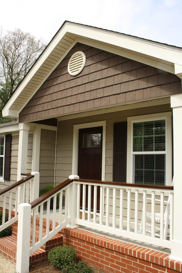 vinyl siding house with white handrail spindles and stained handrail tops on front porch