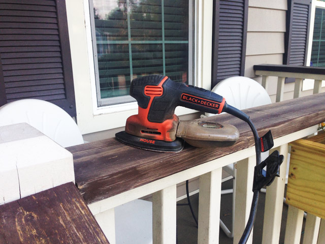 sander sitting on top of stained wood handrails