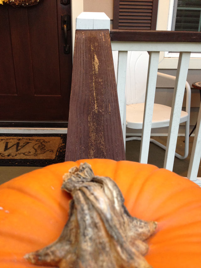 pumpkin in foreground with peeling, crackling stained handrails behind