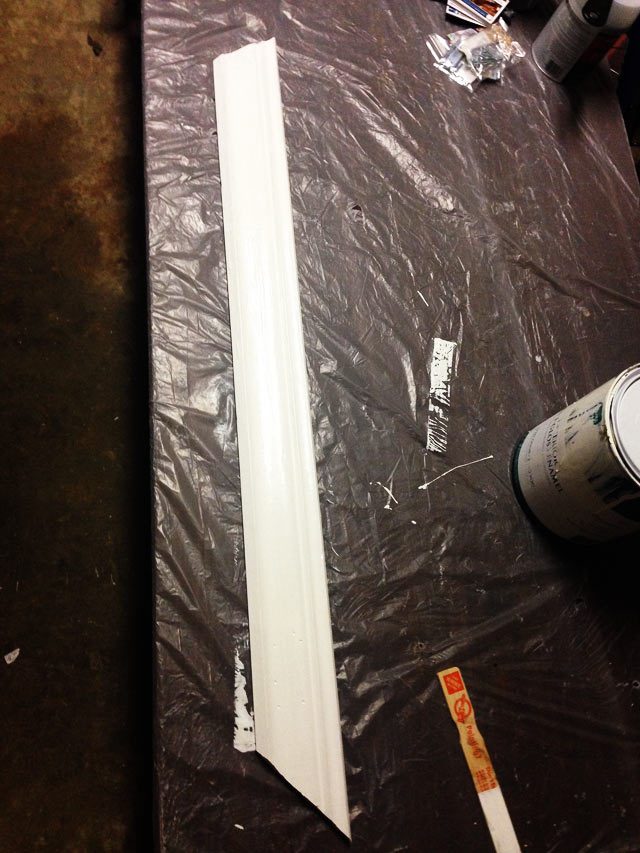 white crown molding sitting on plastic-covered table with paint stir stick