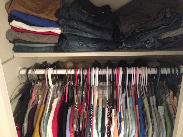 shirts hanging on closet rod with jeans folded on shelf above