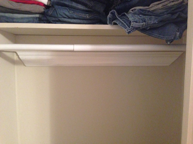 white crown molding on wall under closet rod