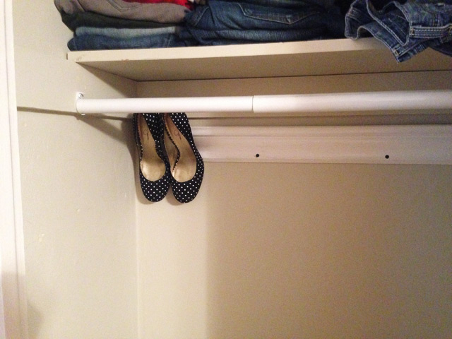 black high heels hanging on white crown molding in closet