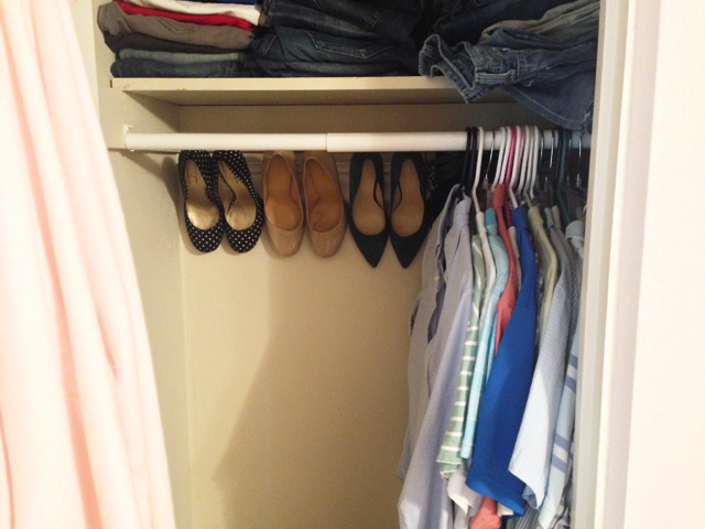 shirts hanging on closet rod with heels on crown molding in the back
