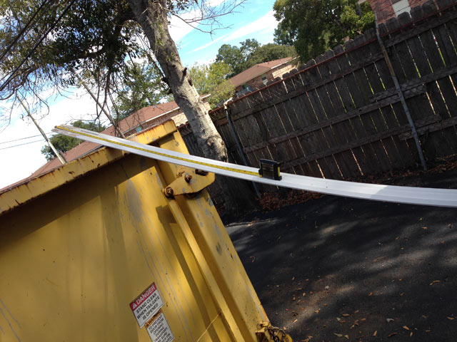 Long piece of white crown molding leaned against yellow dumpster