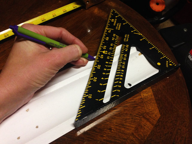pen marking 45 degree angle on white crown molding with speed square