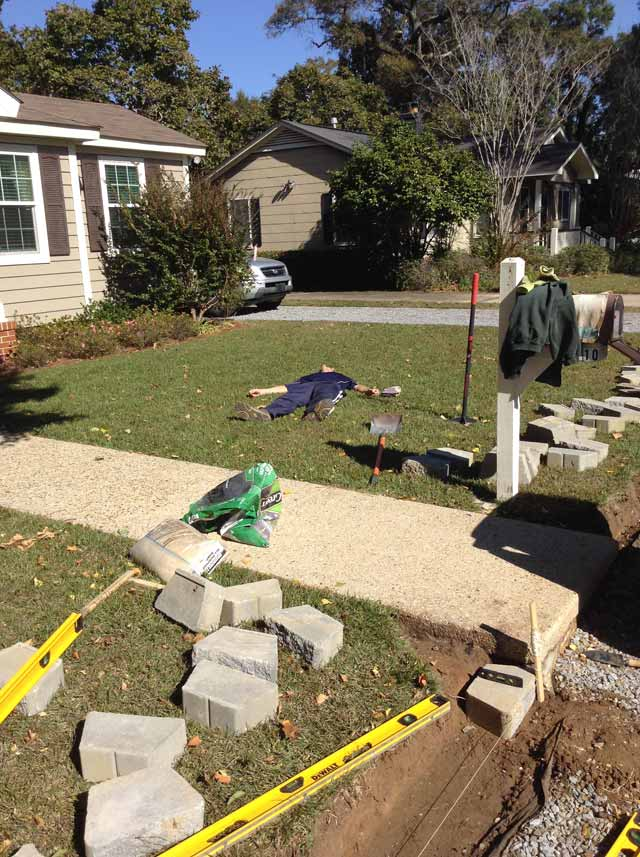 man laying in green grass with retaining wall blocks spread out