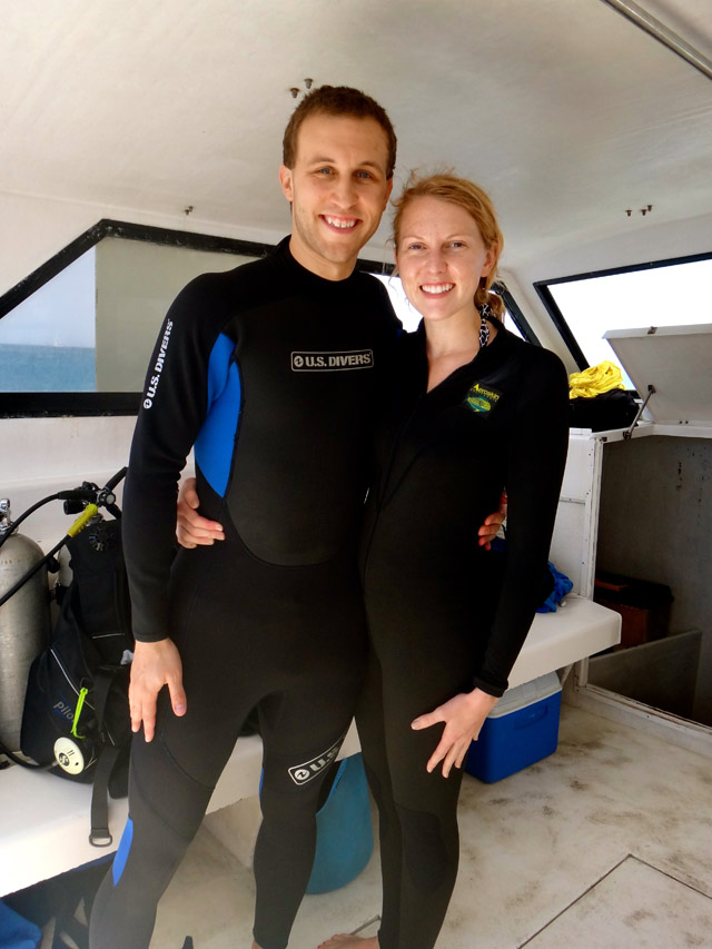 husband and wife in wet suits on boat for scuba diving Grenada