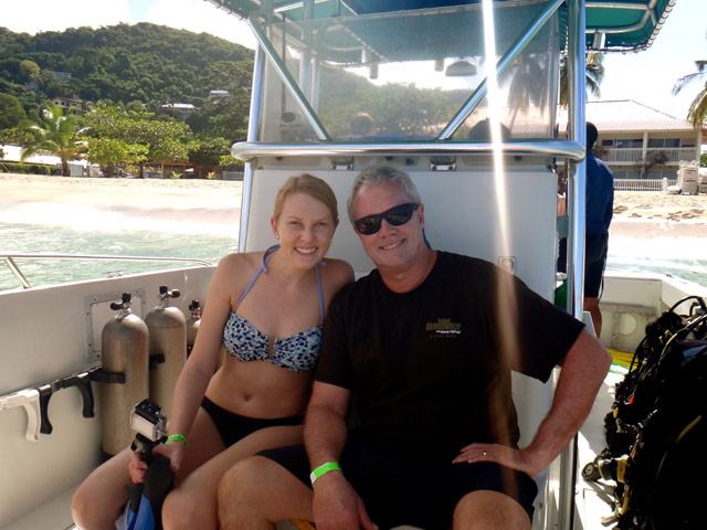 blonde daughter and dad sitting on boat in bathing suits Grenada