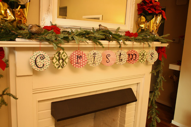DVDs wrapped in scrapbook paper hanging from mantel to spell Christmas with red poinsettias douglas fir garland