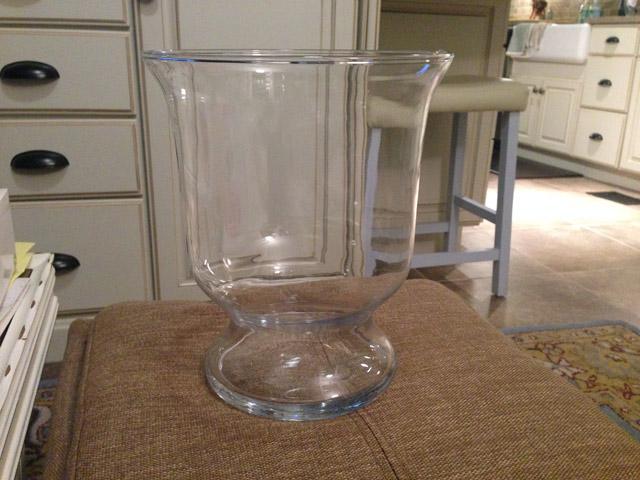 empty glass vase sitting on tan ottoman in sunroom