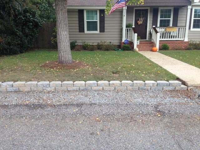 retaining wall on left side of front concrete walkway leading up to tan vinyl siding house with american flag