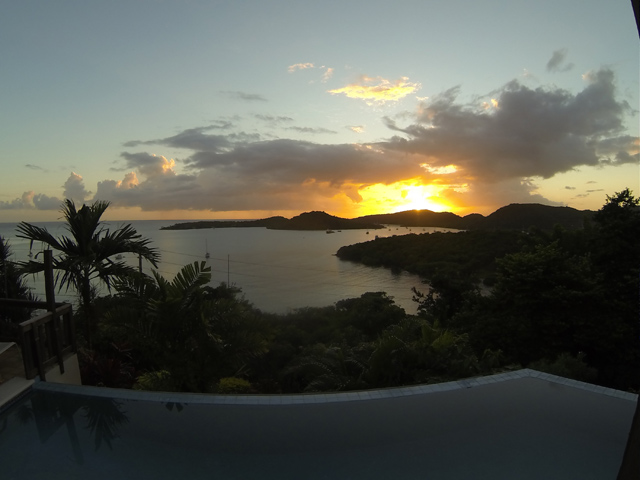 view of sun setting over island from infinity pool with palm trees in foreground