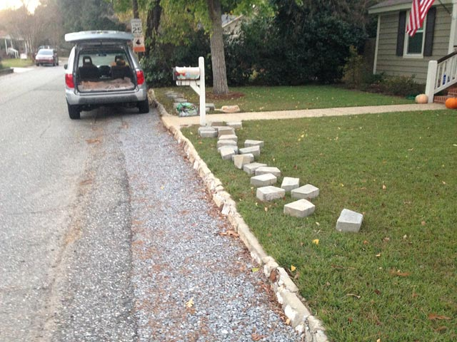retaining wall blocks laid in grass by old retaining wall with green grass