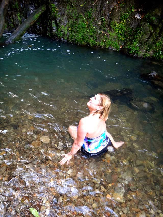 mom in bathing suit sitting in natal pool below seven sisters waterfall Grenada