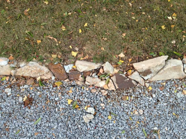 crumbling concrete retaining wall with gravel and grass