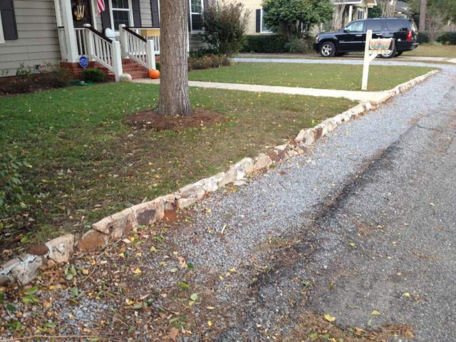 small retaining wall in front of vinyl siding house and asphalt street