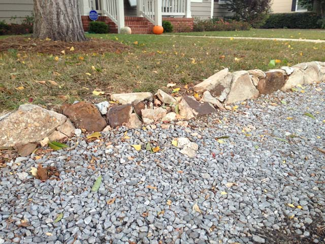 concrete retaining wall in bad shape with gravel and green grass around