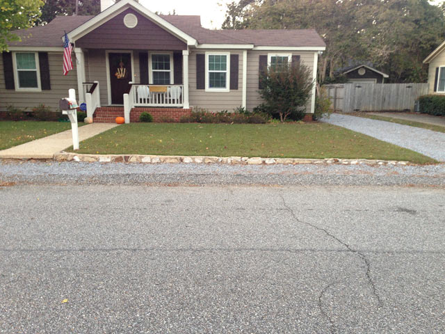 Wide shot of crumbling retaining wall with vinyl siding tan house and green grass