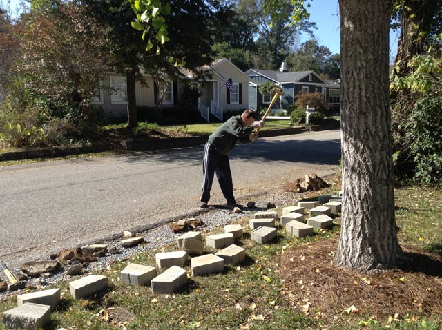 Brandon swinging sledge hammer to tear out old retaining wall