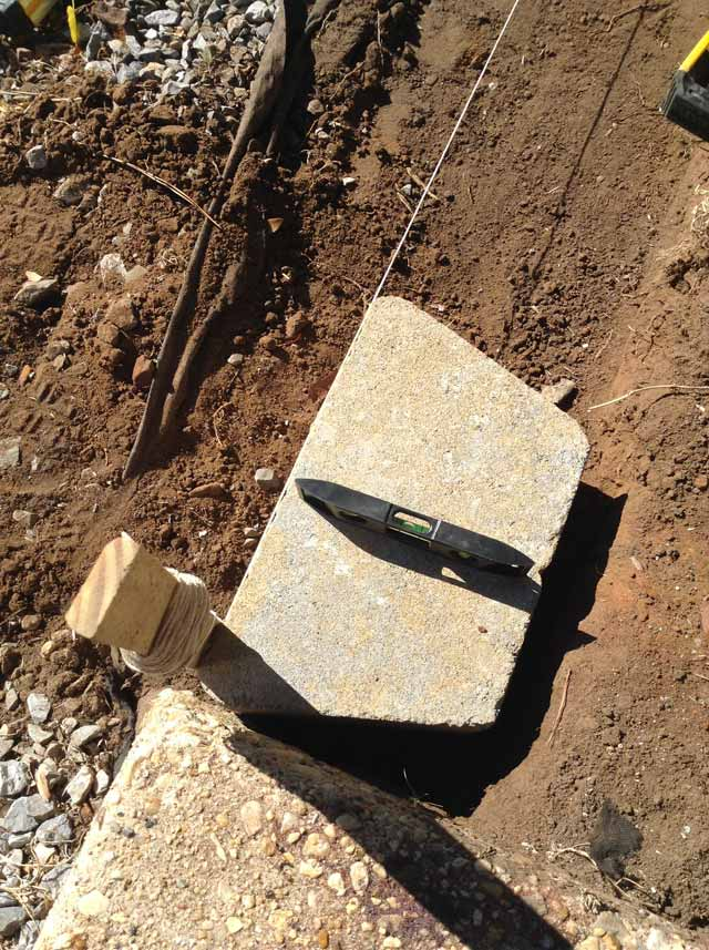 grey concrete block in dirt with small torpedo level on top