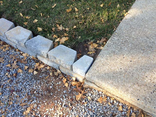 half of retaining wall block in place at sidewalk