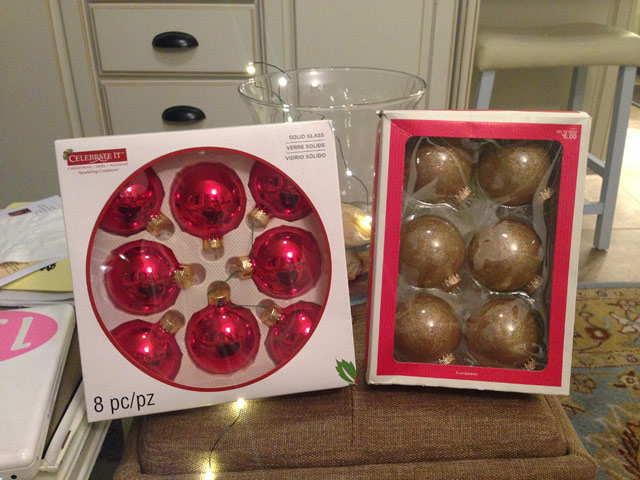 boxes of red and gold Christmas ornaments sitting on tan ottoman in sunroom