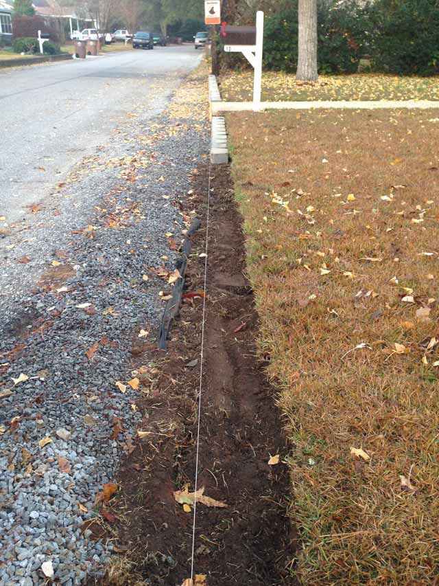 dirt ready for retaining wall blocks in front of dormant grass