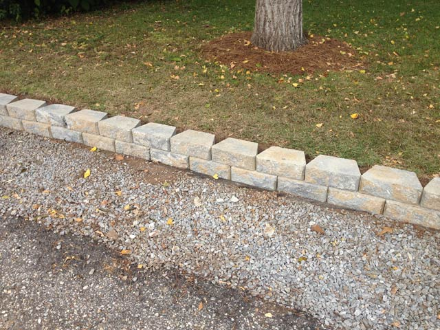 2 rows of retaining wall blocks in place by green grass