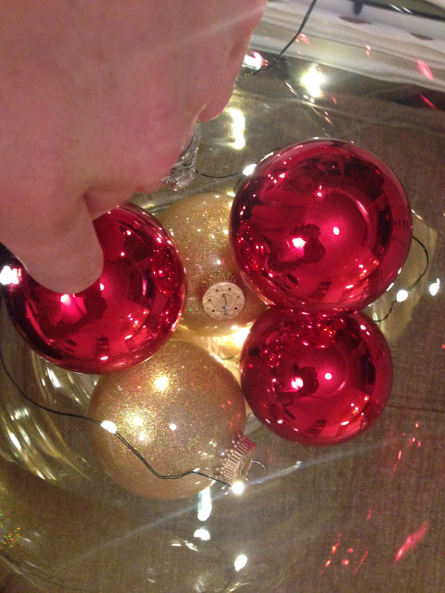 setting red and gold ornaments in glass vase with lights