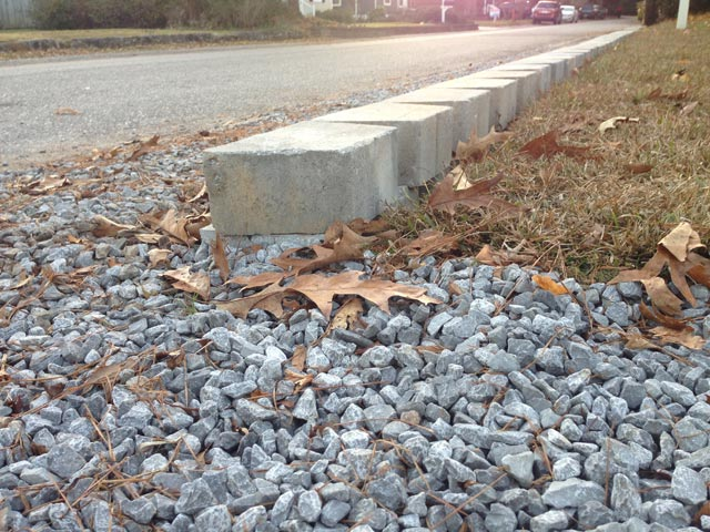 backside of retaining wall at grass and gravel driveway