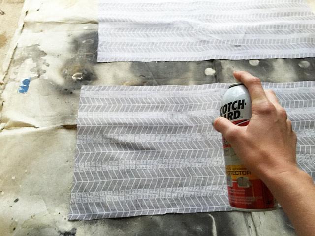 spraying can of Scotchgard on gray greek chevron fabric sitting on dirty drop cloth