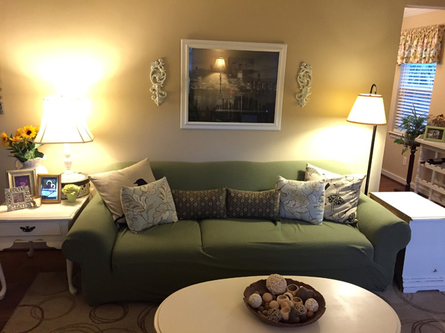 green slipcover on couch in yellow paint living room with sconces and framed poster on wall