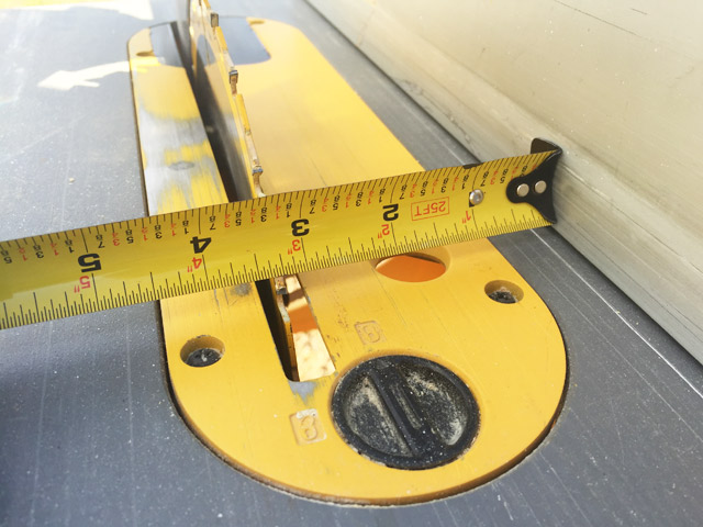 yellow tape measure sitting on yellow table saw measuring 3 and quarter inches