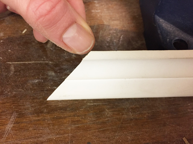 thumb pointing at corner edge of bed molding sitting on workbench