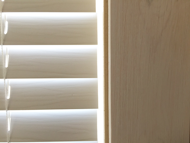 faux wood blinds drawn in window with 1x4 primed trim nailed in place