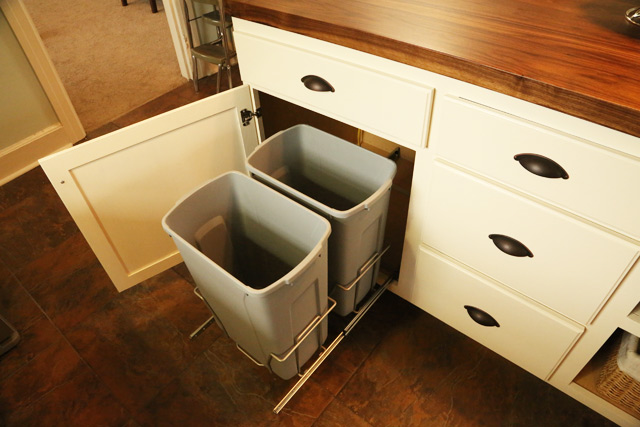 gray trash can pull outs in white kitchen cabinet