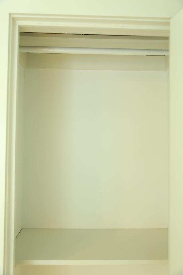 empty white closet with white clothing rod