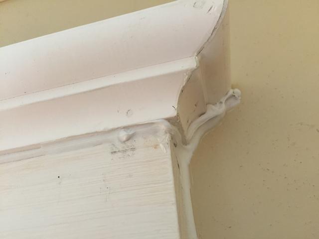 gobs of white latex caulk on bed molding