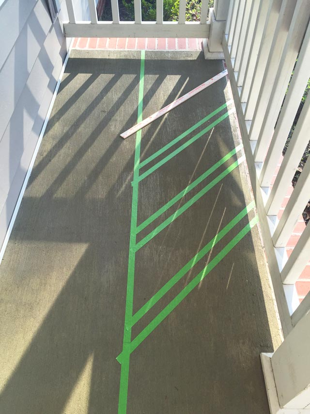 green painter's tape layout design on concrete porch with yardstick